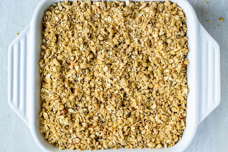 Crisp topped with oats before baking in a square, white casserole dish