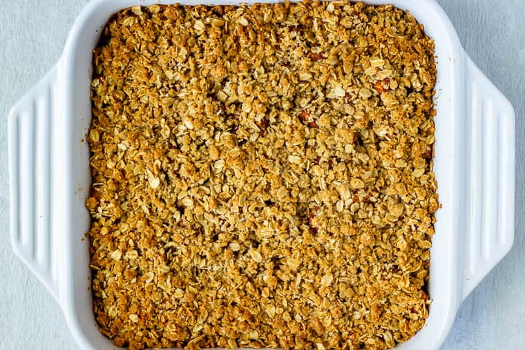 Overhead of baked Apple Cranberry Crisp in a square, white casserole dish