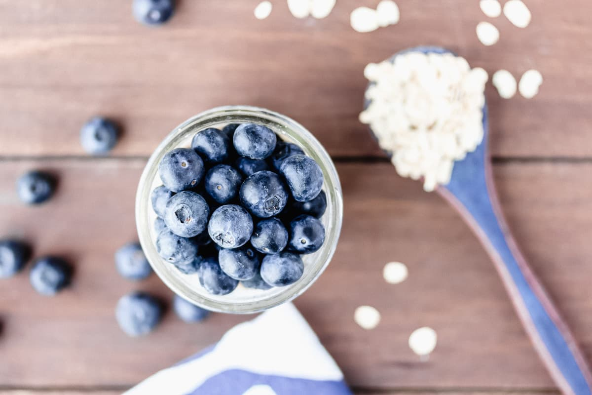 Overhead of blueberry oatmeal in a jar topped with fresh blueberries and and oats and more blueberries scattered around it