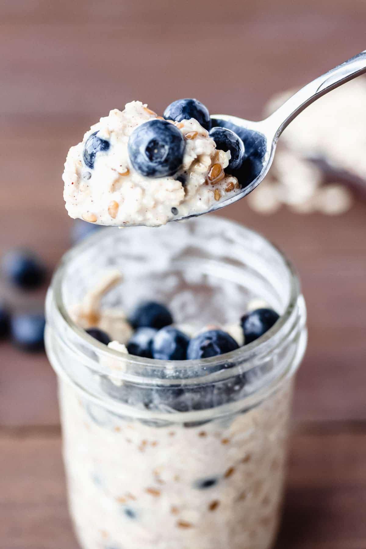 A spoonful of blueberry oatmeal being lifted up over a jar filled with more oatmeal