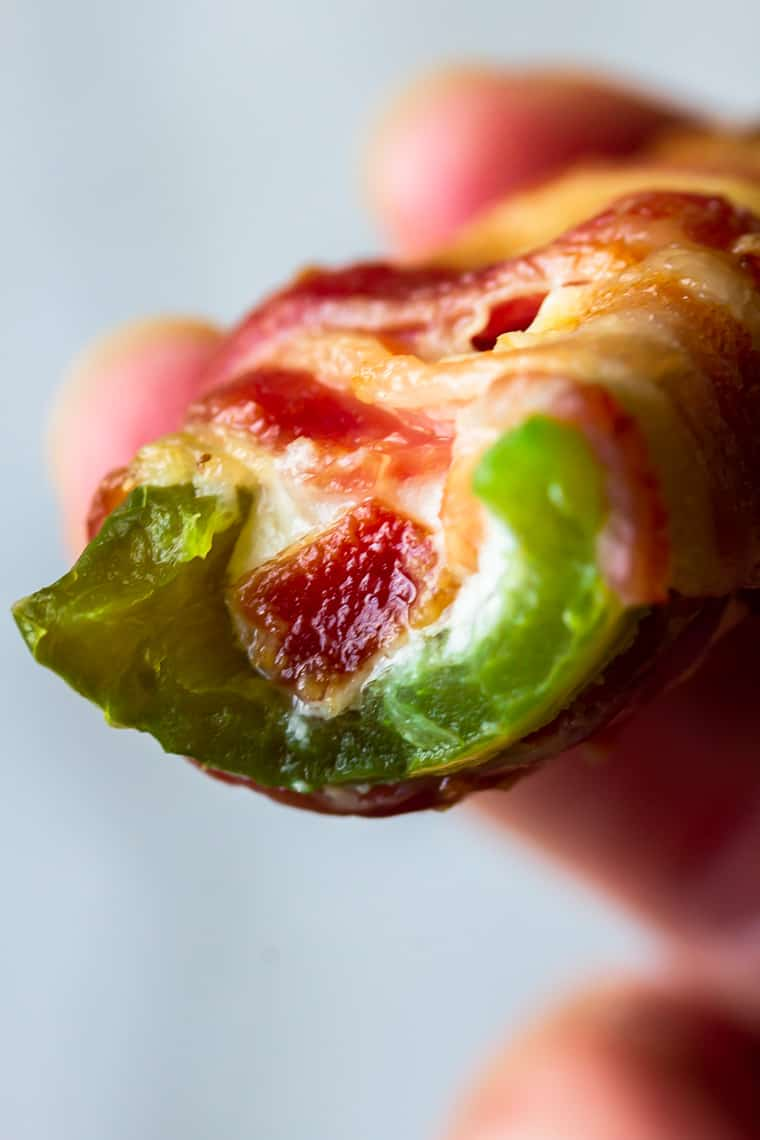 An Extreme Bacon Jalapeno Popper with a bite taken out of it showing the cheese and bacon inside