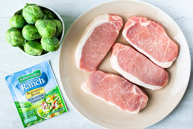 Pork chops, brussels sprouts and a packet of ranch seasoning on a white background