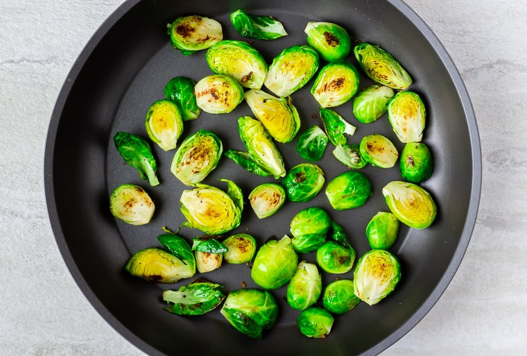 Halved Brussels sprouts cooking in a black skillet over a white background