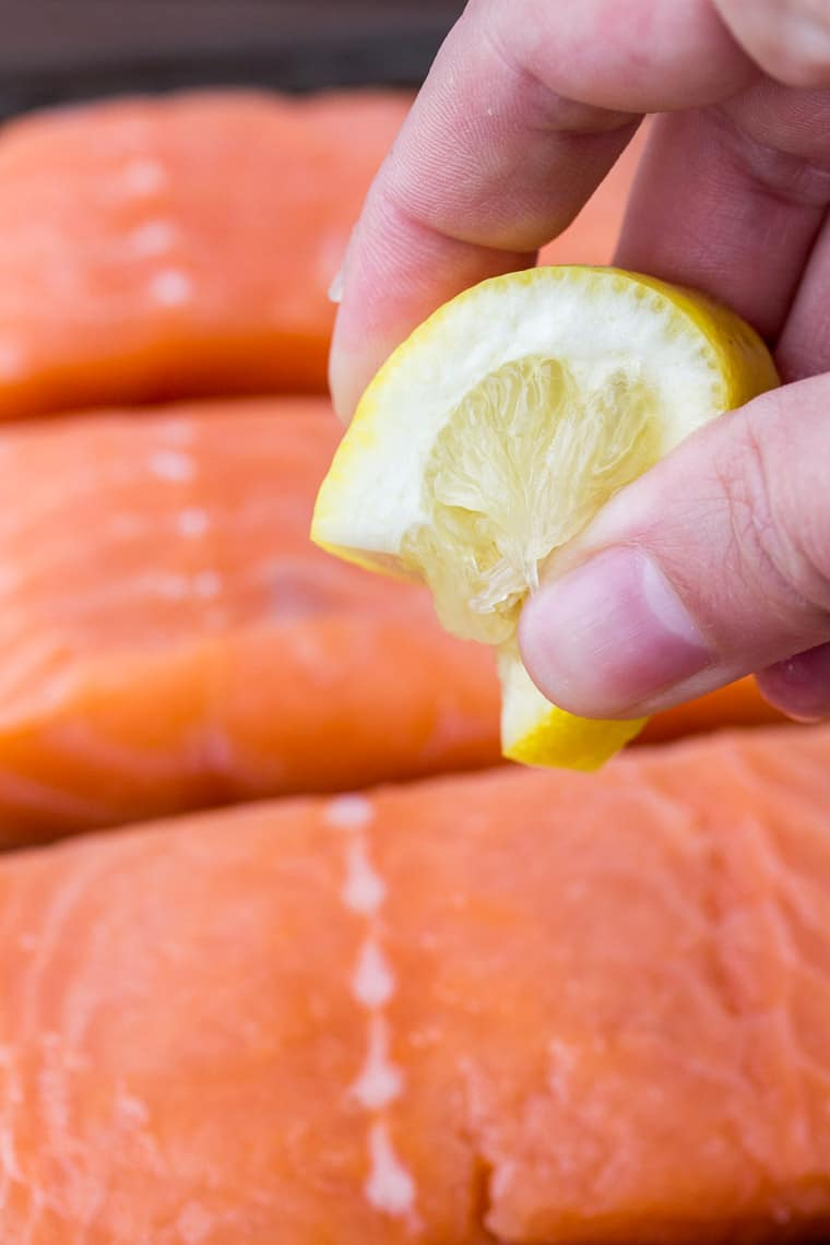 Squeezing Lemon Over the Salmon Fillets