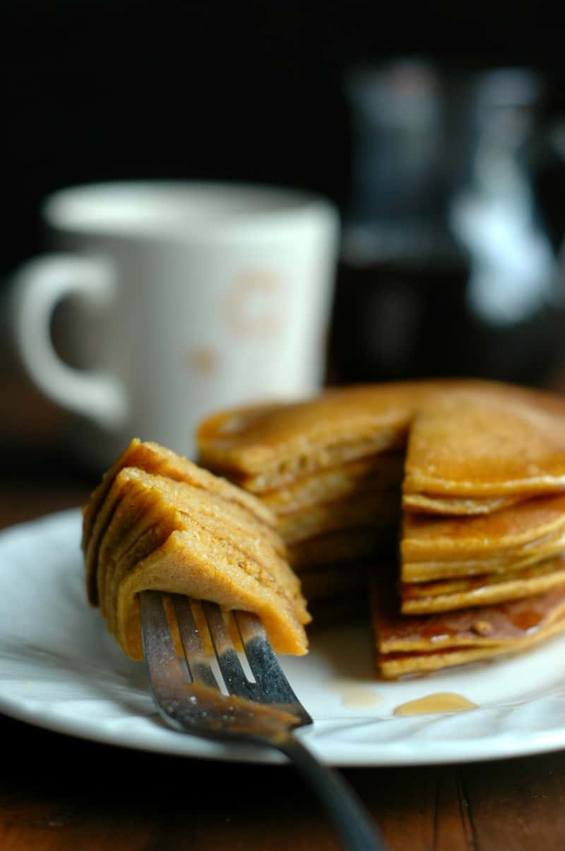 Butternut Pancakes on a White Plate with a Forkful and a White Mug in the background