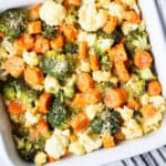 Broccoli, carrots, and cauliflower baked with parmesan bread crumbs in a white casserole dish with a black and white striped napkin