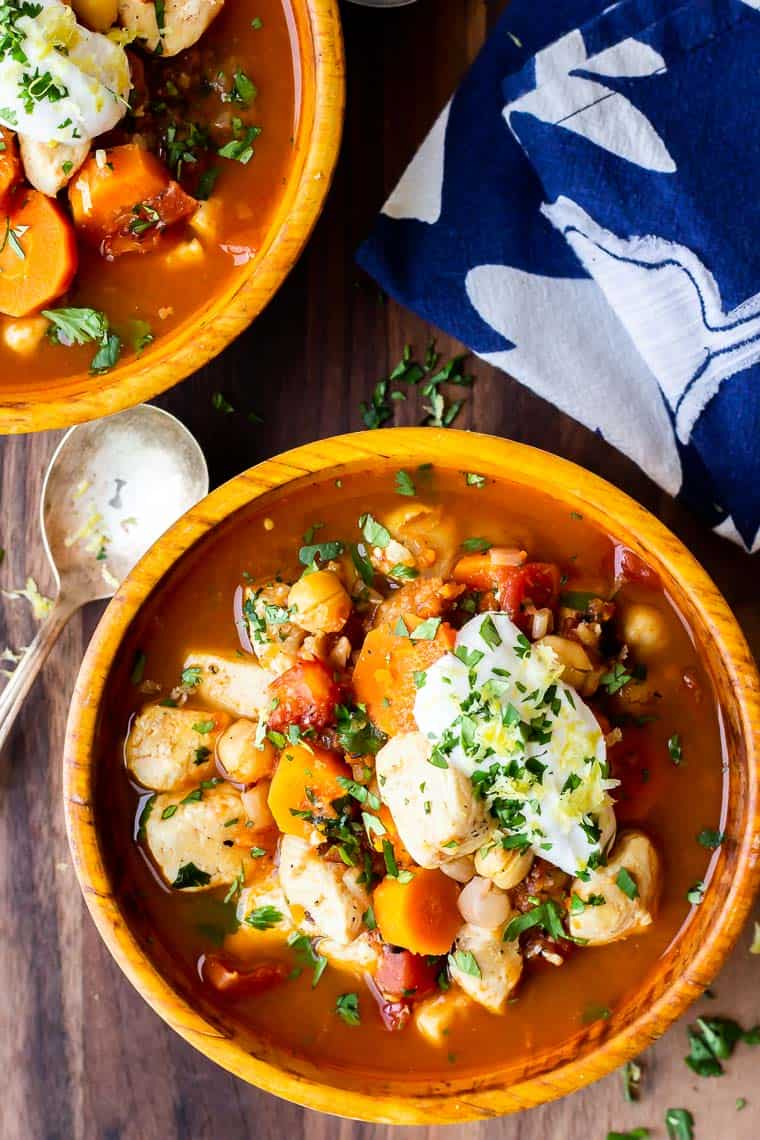 Overhead of 2 bowls of Moroccan chicken stew on a wood board with a blue and white napkin and a spoon next to them