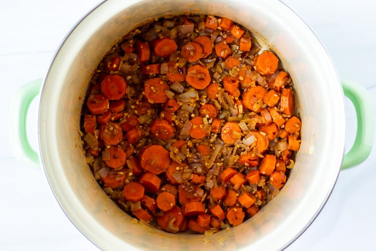 Seasoned carrots and shallot cooking in a stock pot