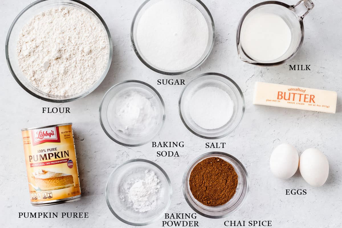 Ingredients to make pumpkin chai coffee cake on a white background with labels