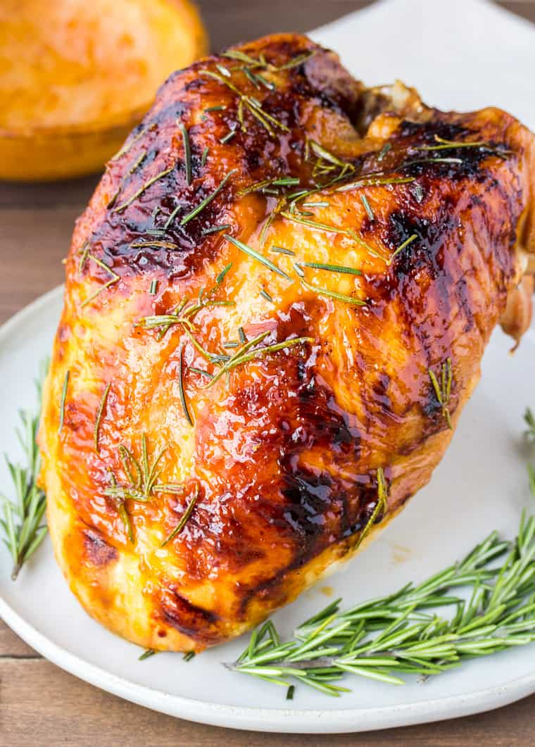 Rosemary Apricot Glazed Turkey with Fresh Rosemary on a White Serving Plate