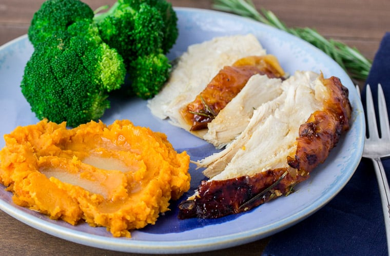 Rosemary Apricot Glazed Turkey Breast Slices on a Blue Plate with Broccoli and Sweet Potatoes