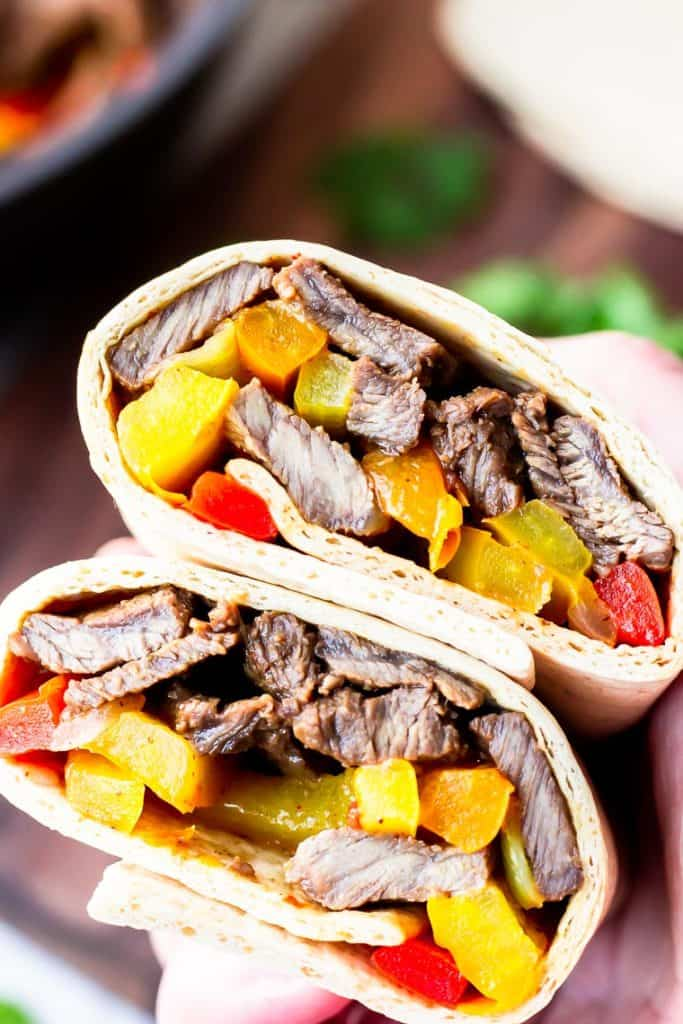 Close up of steak fajitas wrapped in tortillas with a wood board and herbs in the background