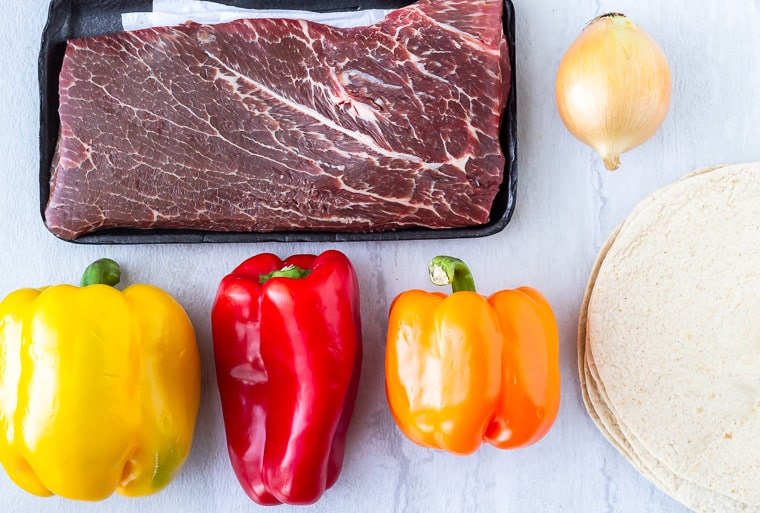 Steak, peppers, onion, and tortillas on a white background