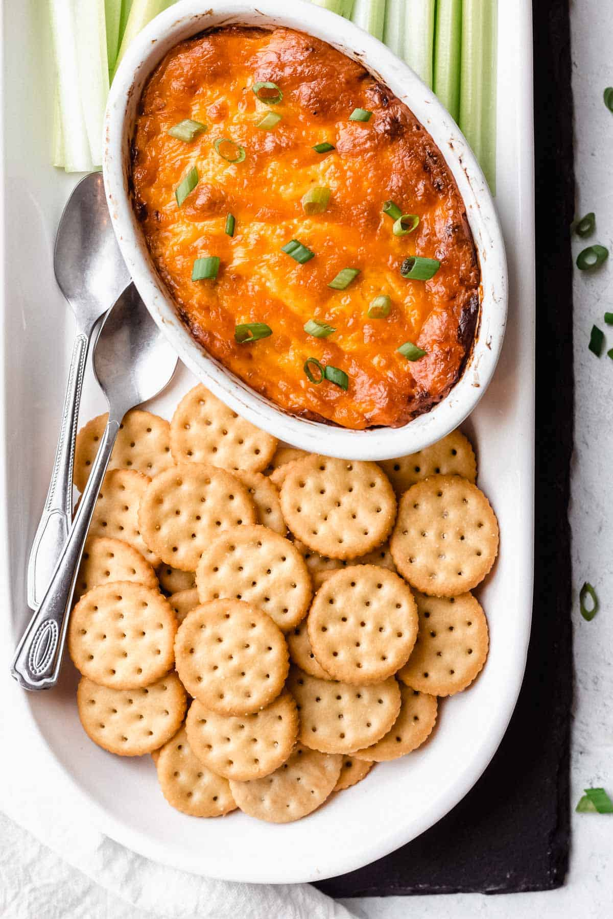 Overhead of barbecue chicken dip in an oval white dish on an oblong dish with crackers, celery sticks, and 2 spoons