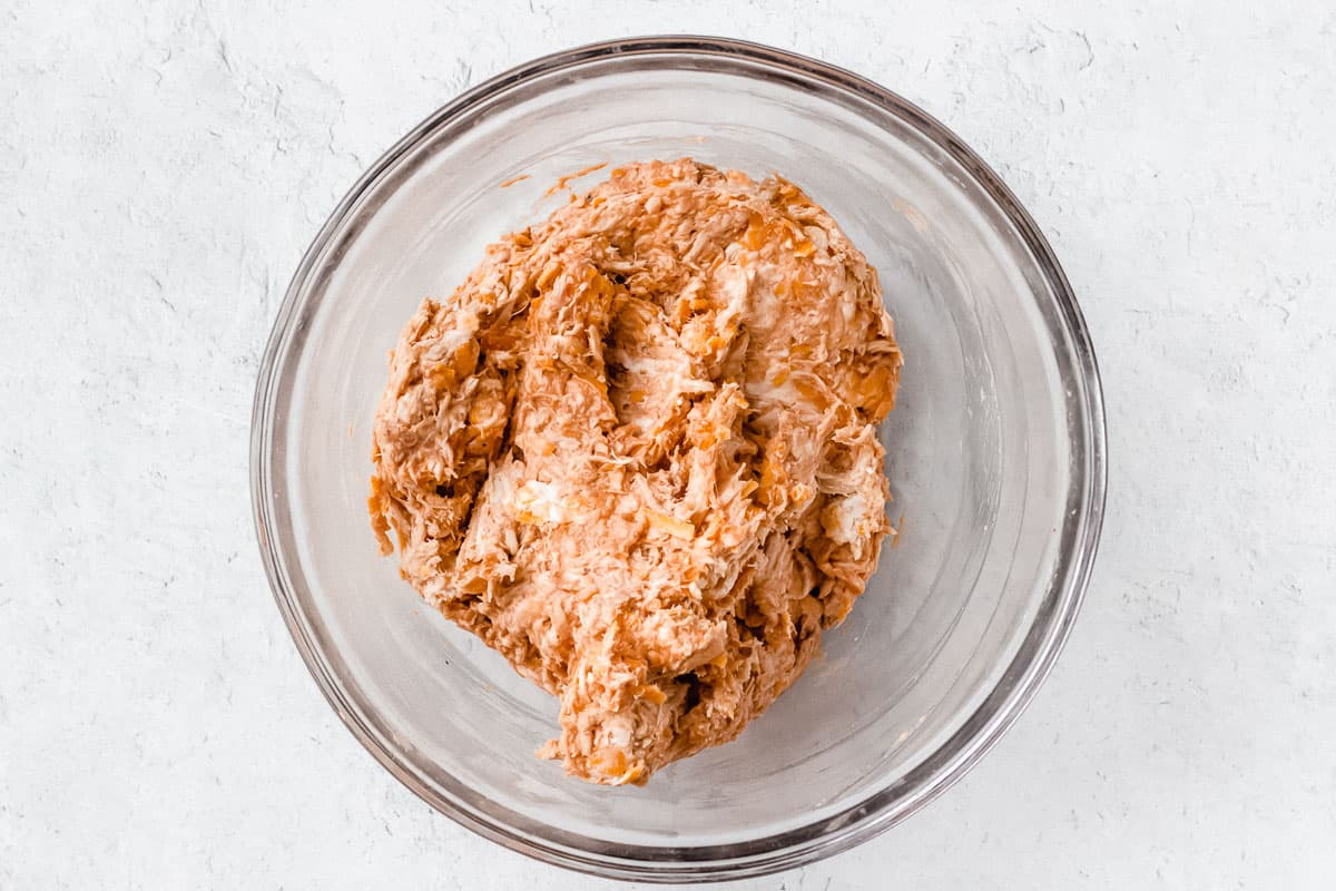 Chicken, cream cheese, cheddar cheese, and barbecue sauce mixed together in a glass bowl over a white background