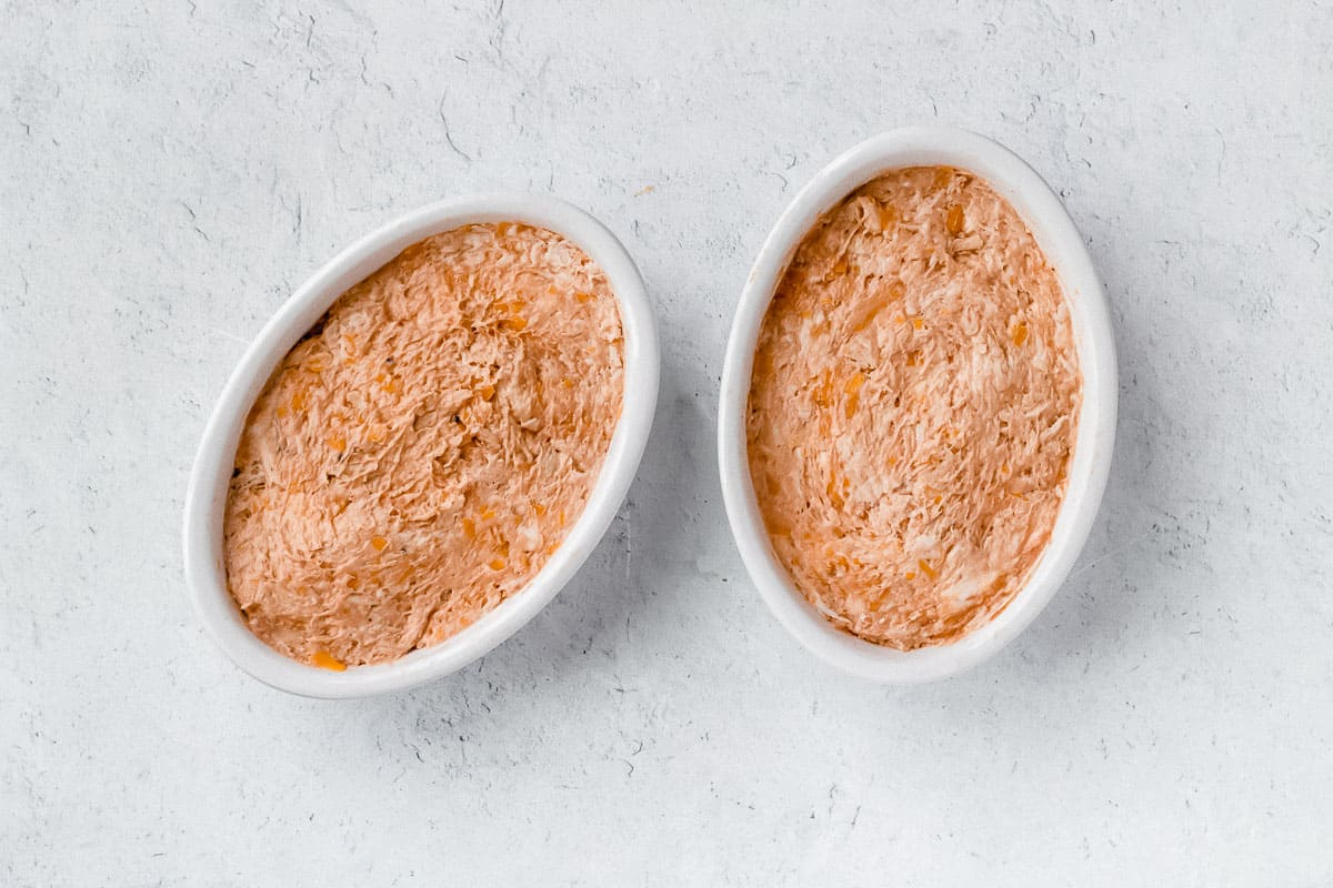 2 small oval baking dishes filled with barbecue chicken dip on a white background