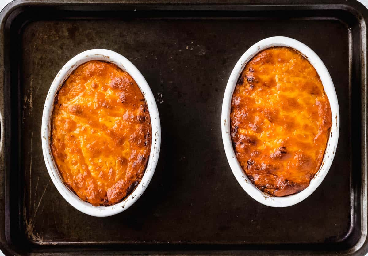 2 smaller oval baking dishes filled with baked barbecue chicken dip on a dark sheet pan