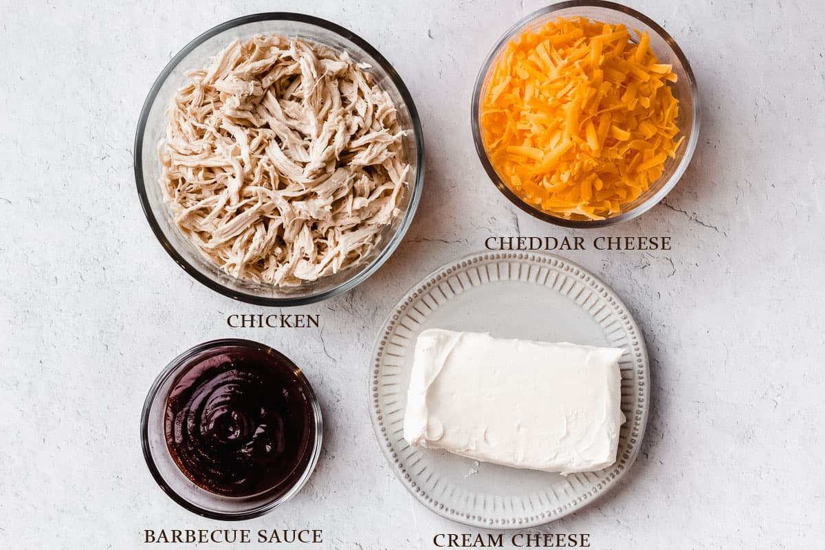 Ingredients to make barbecue chicken dip on a white background with labels