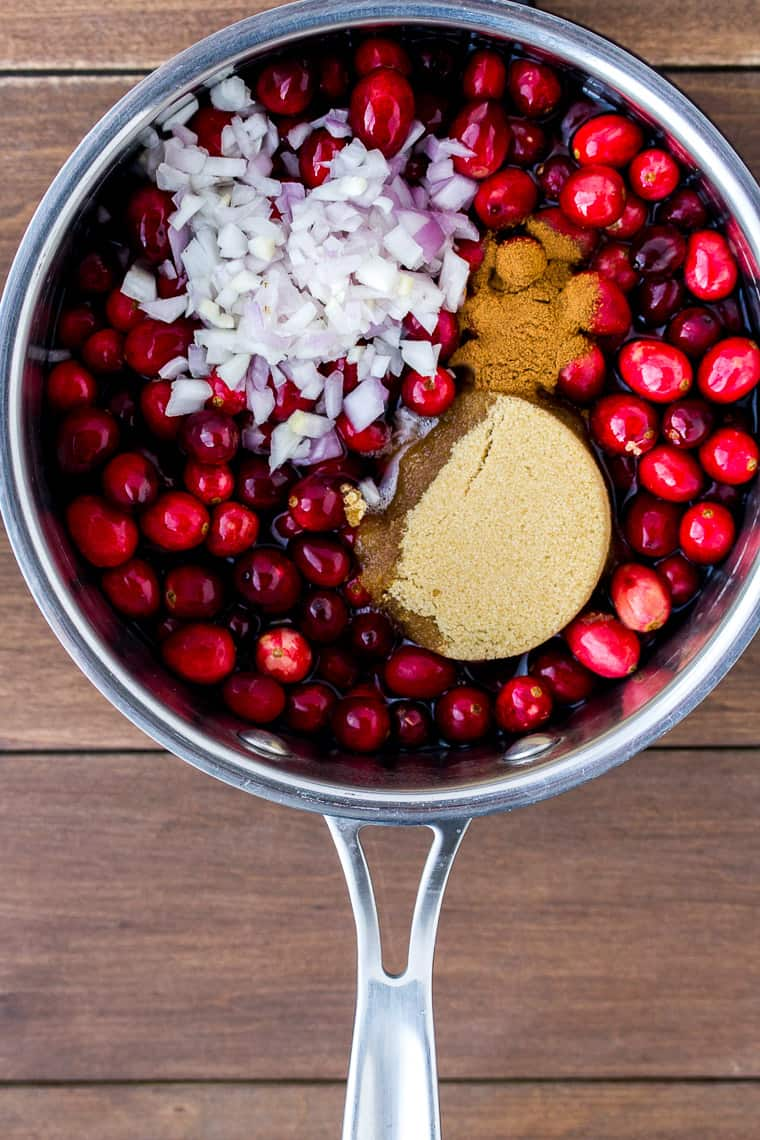 Cranberries, shallot, brown sugar, and cinnamon in a silver pot