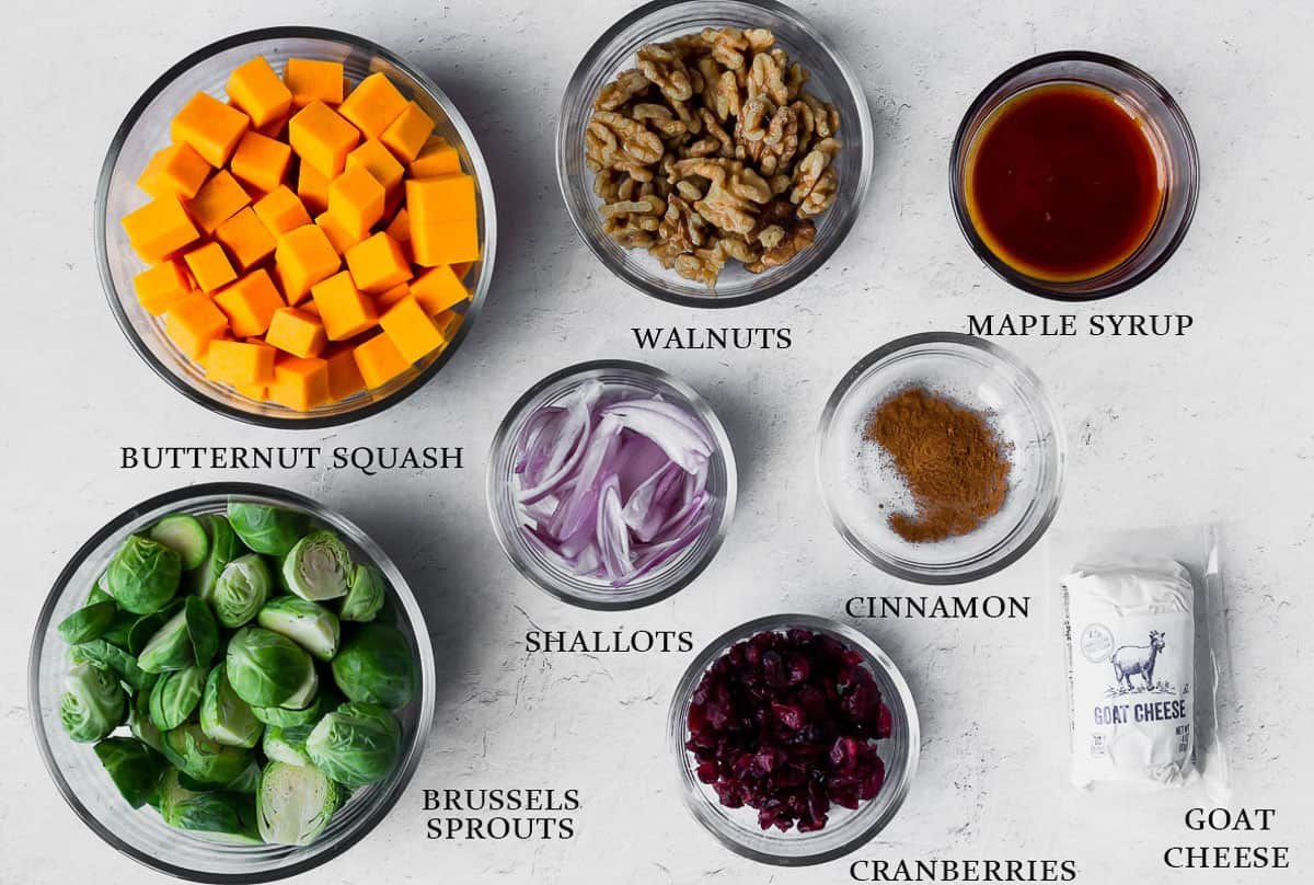 Ingredients for roasted butternut squash with brussels sprouts, cranberries, and maple walnuts on a white background
