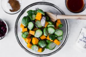 Brussels sprouts, butternut squash and shallots in a glass bowl with a wood spoon