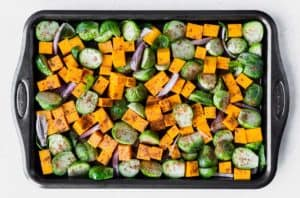 Butternut squash cubes, brussels sprouts and shallots on a baking sheet