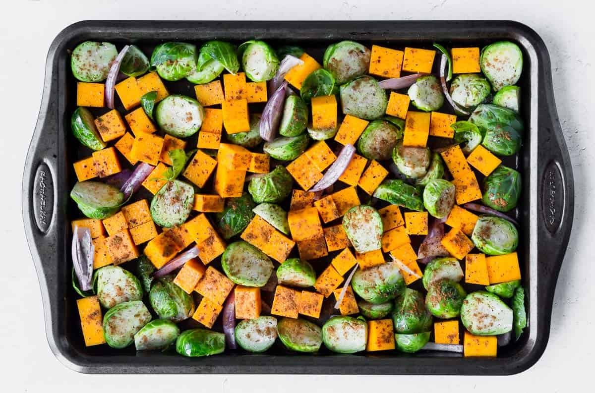Butternut squash cube, brussels sprouts and shallots on a baking sheet