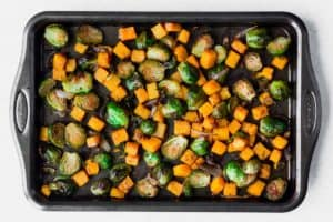 Roasted Brussels sprouts, butternut squash and shallots on a baking sheet