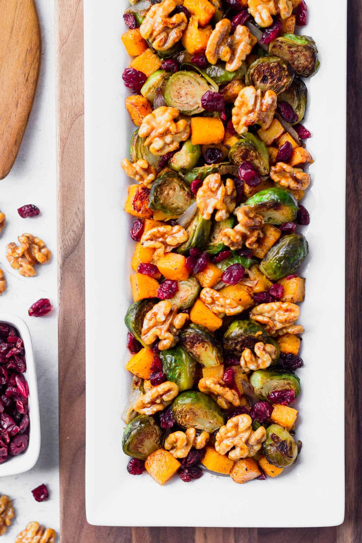 Overhead of roasted fall vegetables including butternut squash, brussels sprouts, cranberries and walnut on a rectangular white plate over a white board with extra cranberries and walnuts on the side
