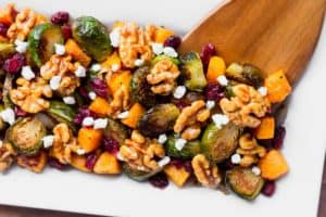 Roasted Fall Vegetables with cranberries, maple walnuts, and goat cheese on a white plate