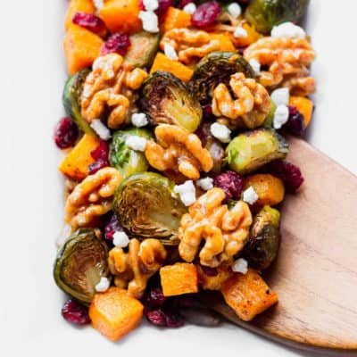 Roasted Butternut Squash medley with brussels sprouts, cranberries, walnuts, and goat cheese with a spatula lifting some up