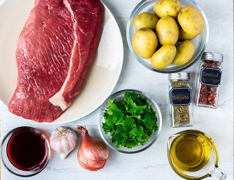 Ingredients to make chimichurri steak on a white background