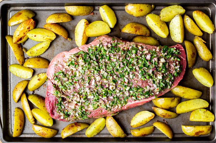 Partially roasted potatoes on a baking sheet with a large piece of steak in the middle