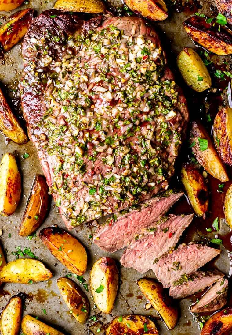 Overhead of sheet pan steak and potatoes with chimichurri sauce and a few slices of steak cut off next to it