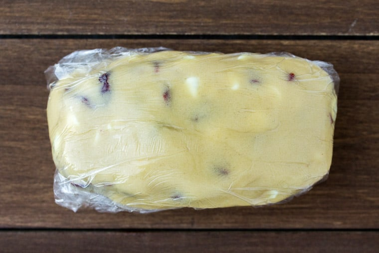 Cookie dough wrapped in plastic wrap on a wood board