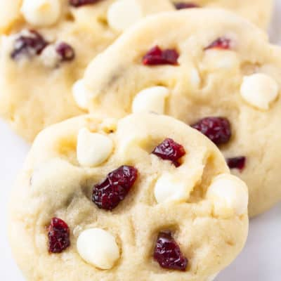 Close up of 4 white chocolate chip cranberry cookies on a white background