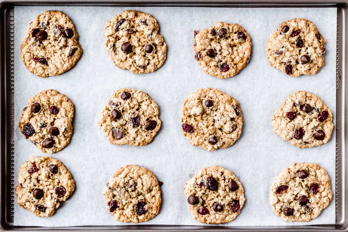 Baked oatmeal cranberry chocolate Chip cookies on a parchment paper lined baking sheet