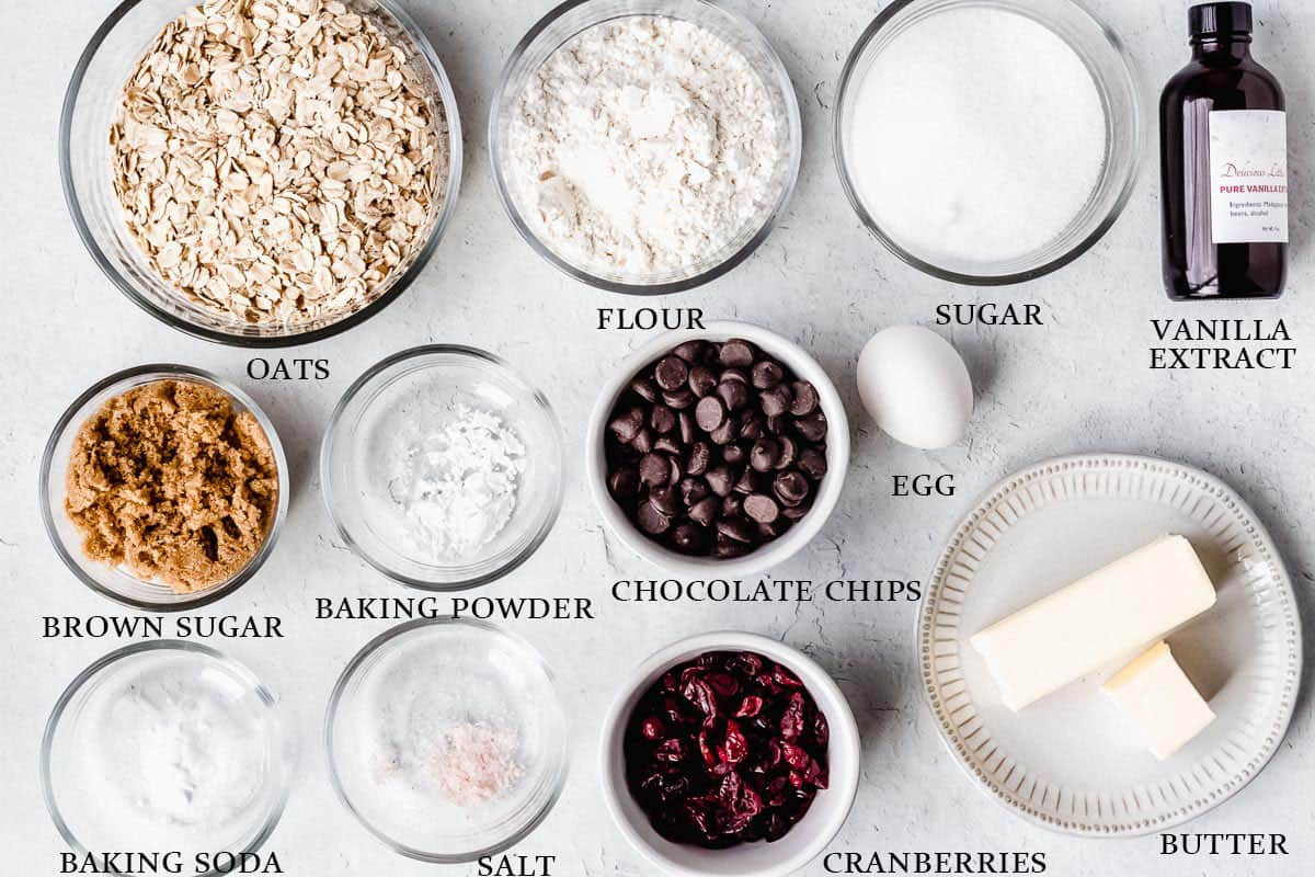Ingredients to make cranberry chocolate chip oatmeal cookies on a white background with labels