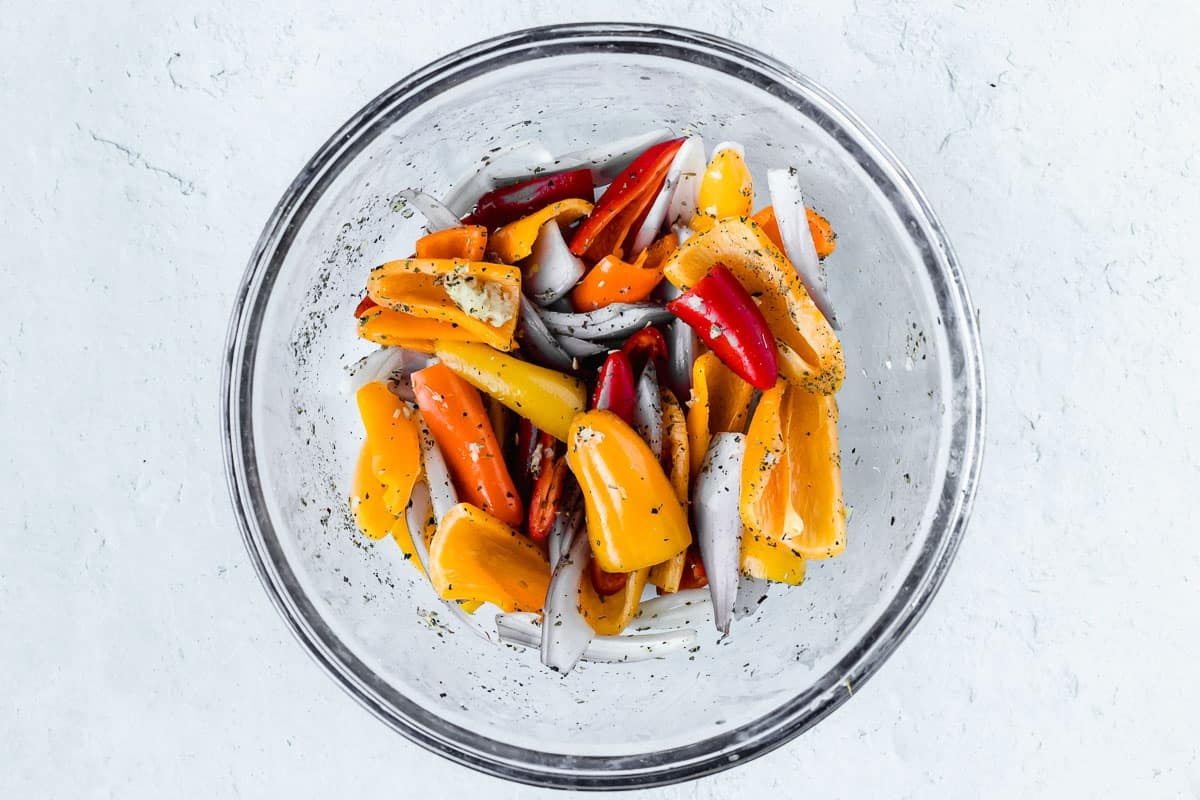 Seasoned peppers and shallots in a glass bowl over a white background