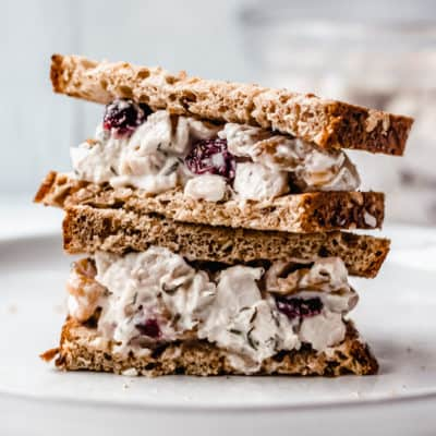 Cranberry Walnut chicken salad sandwich cut in half and stacked on top of each other on a white plate with a gray background