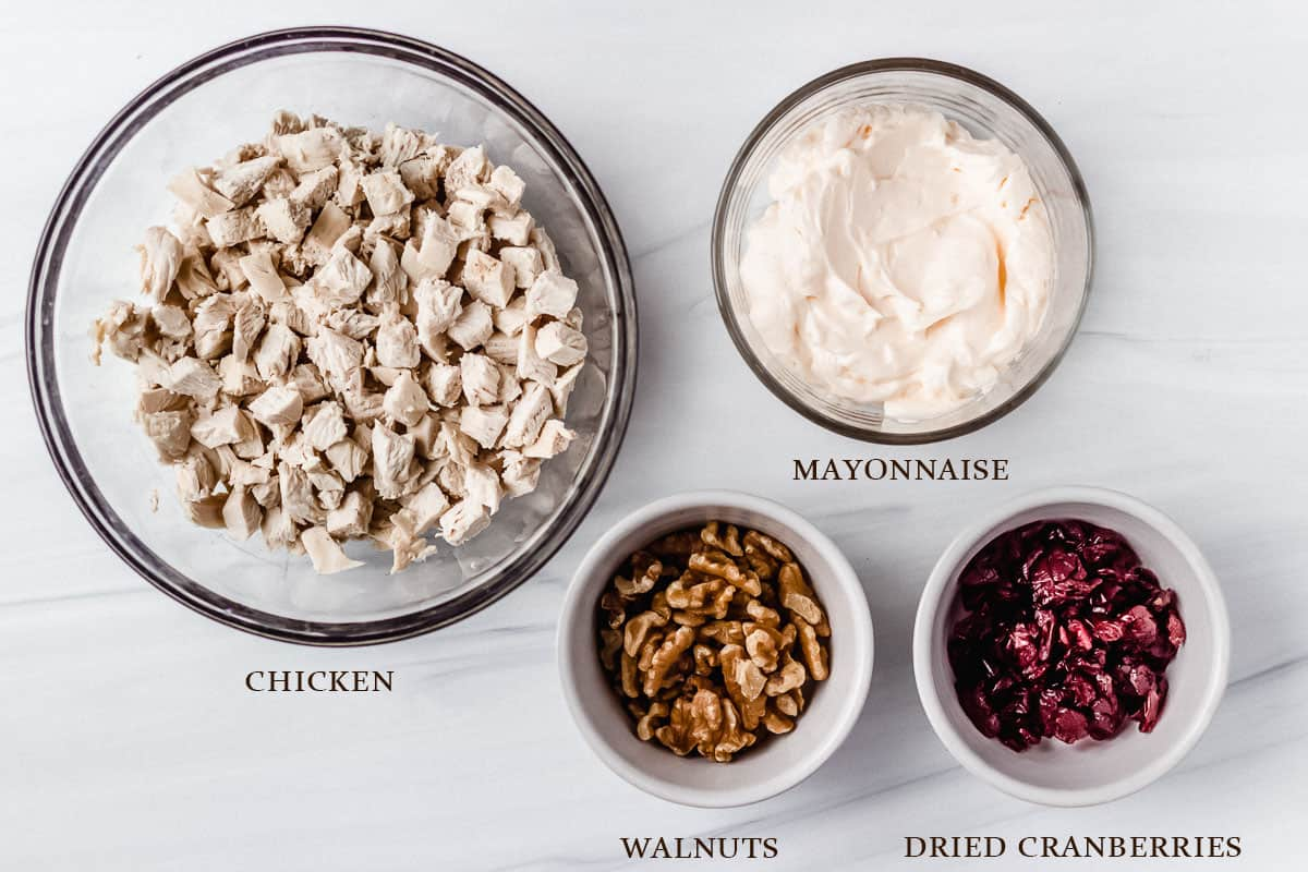 Ingredients needed to make cranberry chicken salad on a white background with labels