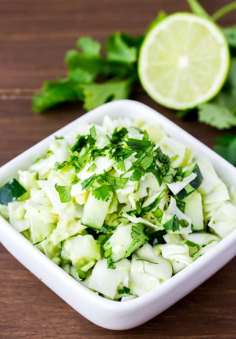 Keto Avocado Cabbage Slaw in a White Serving Dish with Cilantro and Lime