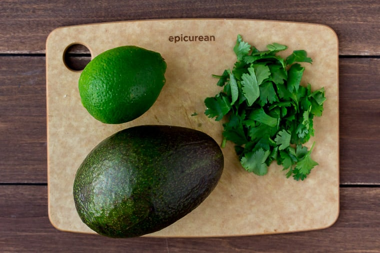 A Cutting Board with Avocado, Cilantro, and Lime on it
