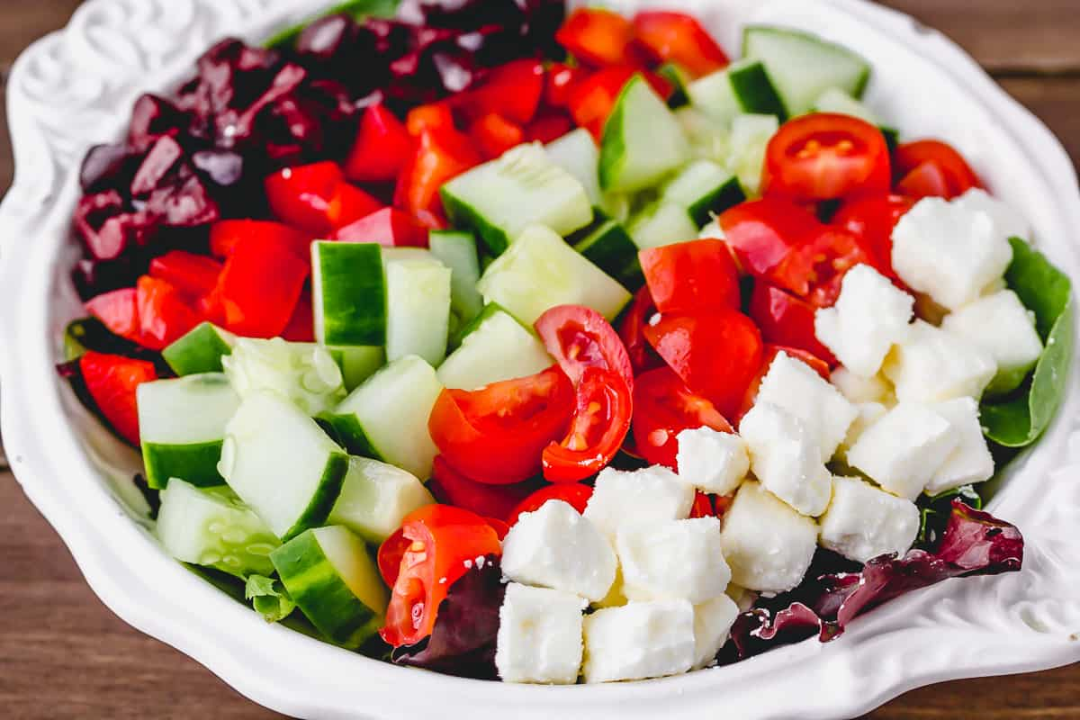 Keto greek salad in a white bowl over a wood background