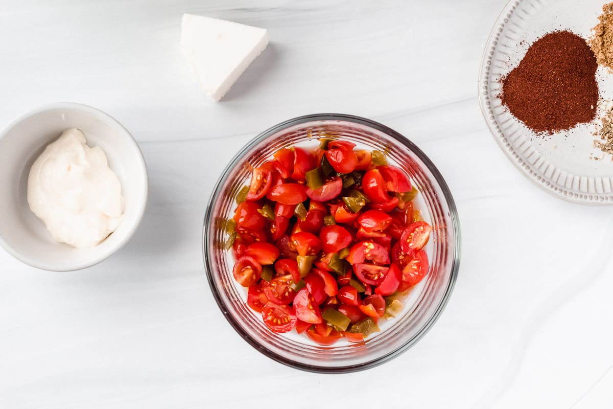 Tomatoes and jalapeno peppers diced in a glass bowl with a plate of spices, a piece of queso cheese and a white bowl of mayonnaise on a white background
