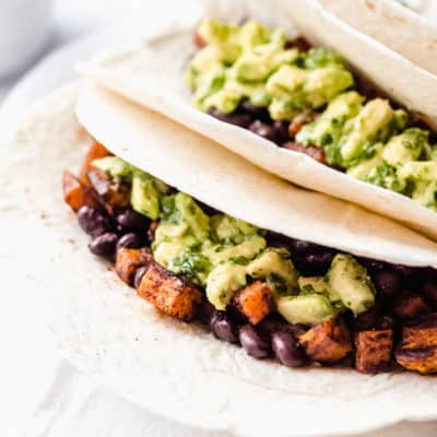 Sweet potato black bean tacos on a white plate close up