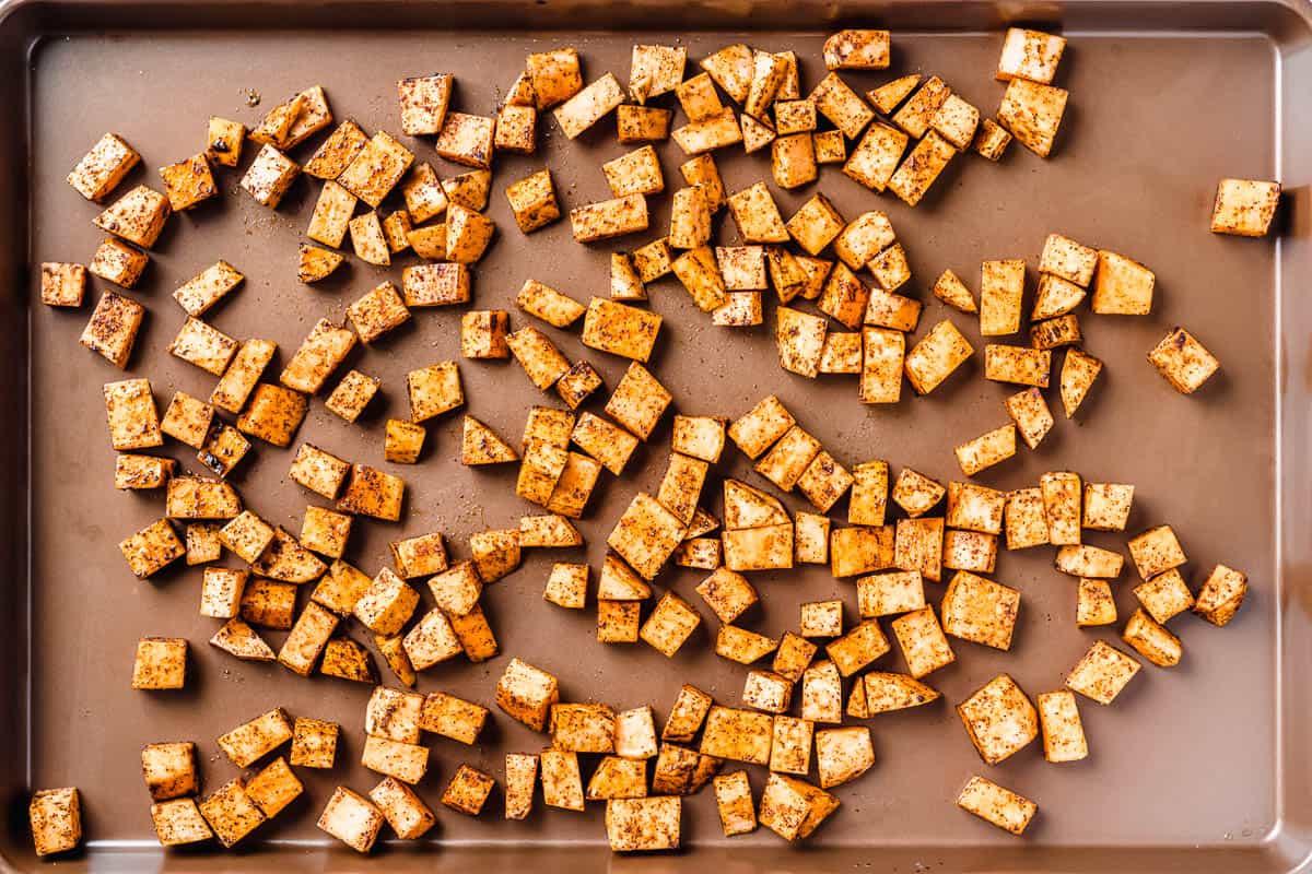 Seasoned sweet potato cubes on a copper baking sheet