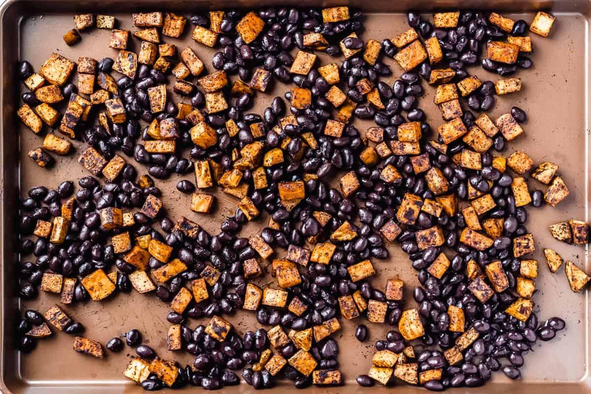 Seasoned sweet potatoes and black beans on a copper baking sheet