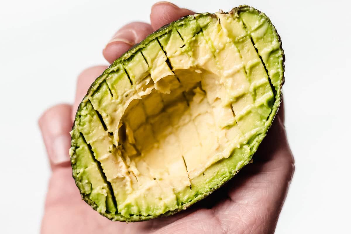 An avocado half sliced into small cubes.