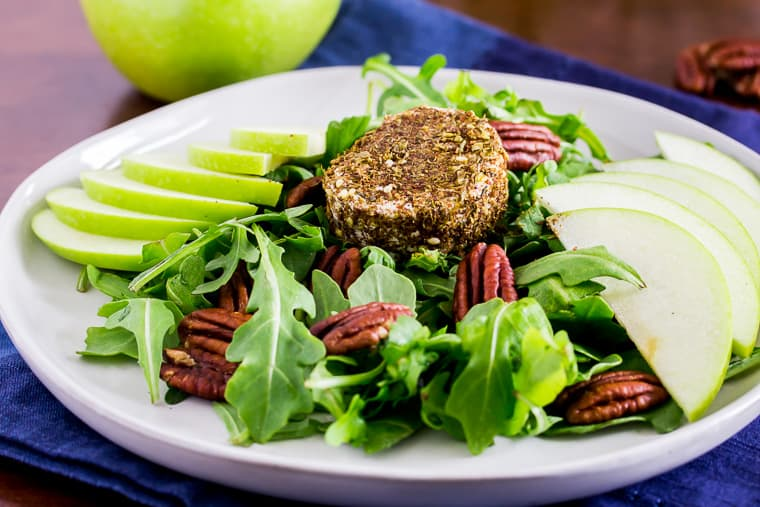 A Close up of Za'atar Crusted Goat Cheese onto of Arugula with pecans and apple slices on a white plate with a blue napkin, apple ,and pecans in the background